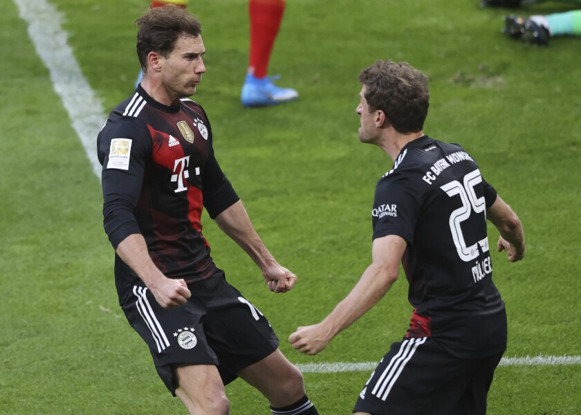 Bayern's Leon Goretzka, left, celebrates with teammate Bayern's Thomas Mueller, after scoring the opening goal of the game during the German Bundesliga soccer match between RB Leipzig and Bayern Munich, in Leipzig, Germany, Saturday, April 3, 2021. (Alexander Hassenstein/ Pool via AP)