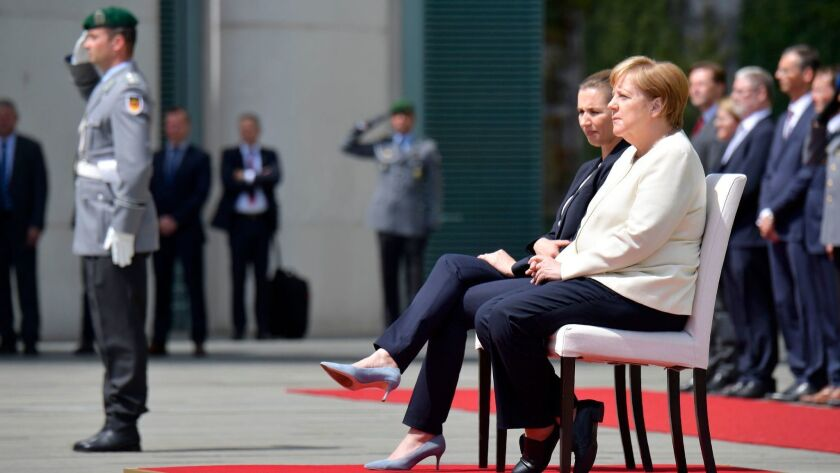 German Chancellor Angela Merkel, right, and Danish Prime Minister Mette Frederiksen sit as they listen to the national anthems during a welcoming ceremony with military honors on July 11, 2019, in the courtyard of the Chancellery in Berlin.
