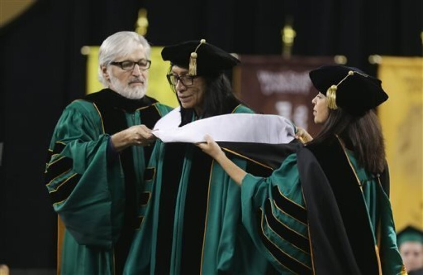 """Wayne State University Board of Governors Paul Massaron, left, and Sandra Hughes O'Brien confer a Doctor of Humane Letters honorary degree to Sixto Rodriguez, Thursday, May 9, 2013 in Detroit, during the university's commencement. Rodriguez's two albums in the early 1970s received little attention in the United States but he unknowingly developed a cult following in South Africa during the apartheid era. He was the subject of an Oscar-winning documentary, """"Searching for Sugar Man."""".(AP Photo/Car"""