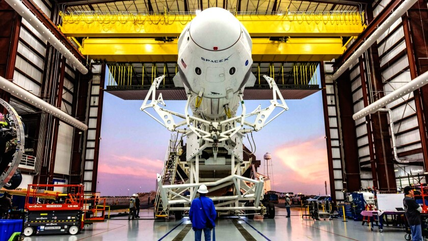 SpaceX's Falcon 9 rocket, with its Crew Dragon capsule attached, rolls out of the company's hangar a