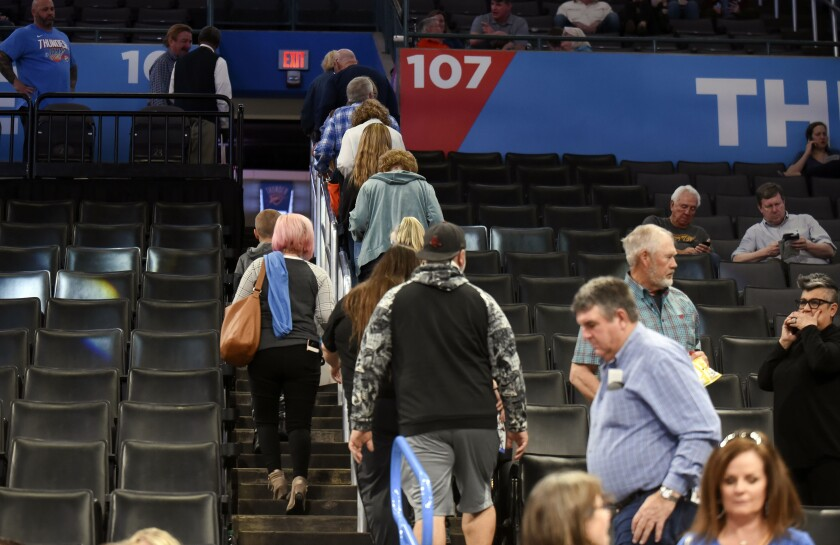 Basketball fans leave Chesapeake Energy Arena after Wednesday's game between the Oklahoma City Thunder and Utah Jazz was postponed.