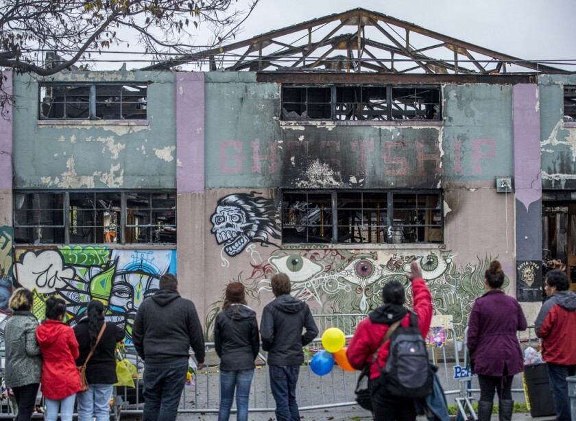 People look at the remains of the Ghost Ship warehouse in Oakland on Dec. 10, 2016, a little more than a week after the fire that killed 36 people.