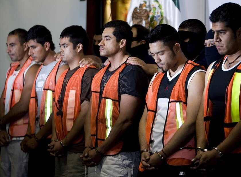 Police officers guard alleged drug trafficker Isaac Godoy, third right, during his presentation to the media in Mexico City, Thursday, April 23, 2009. Godoy, who allegedly ran operations for the Arellano Felix drug cartel, was arrested Tuesday in Tijuana, northern Mexico, along with six other alleg