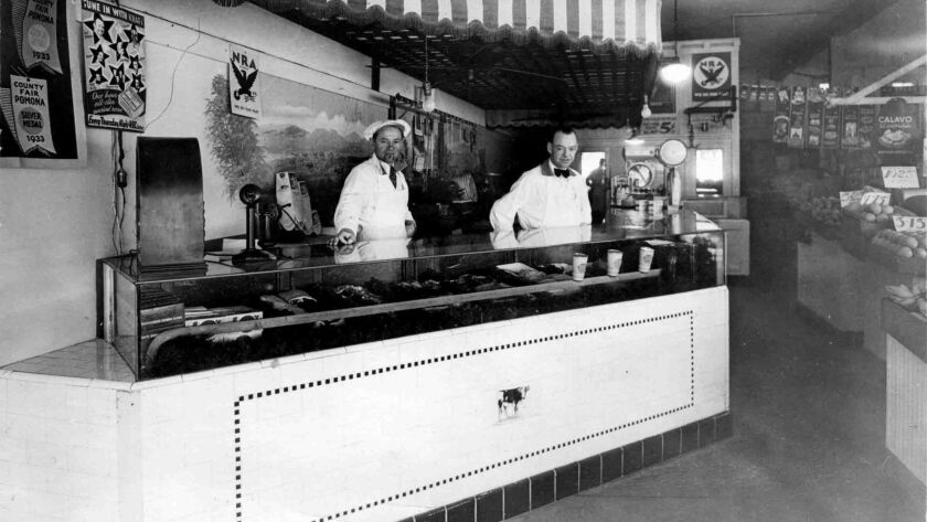 Phillip Mislay, left, stands behind the counter of the market in the Five Points building. (Courtesy