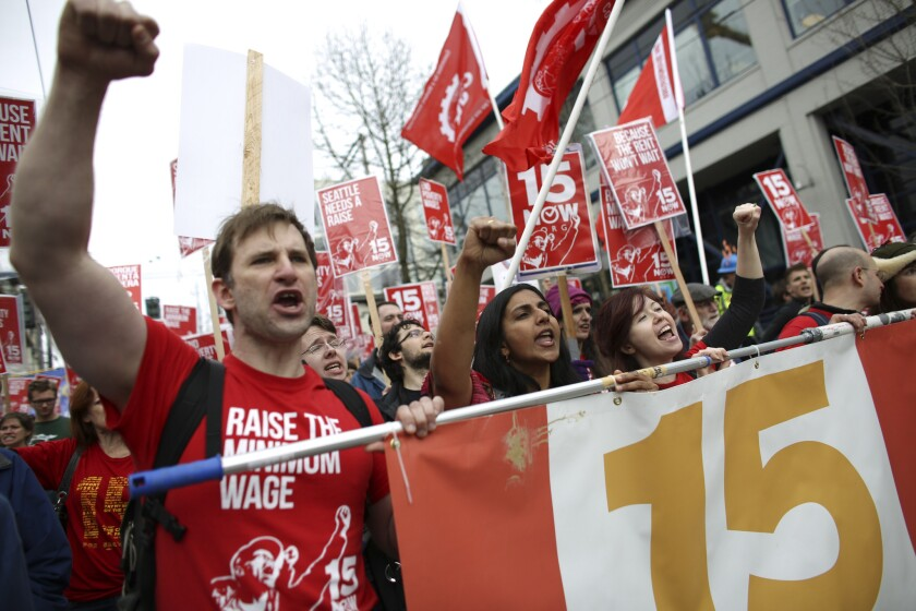 Organizer Bryan Watson, left, gestures during a march to raise the minimum wage to $15 per hour in Seattle.