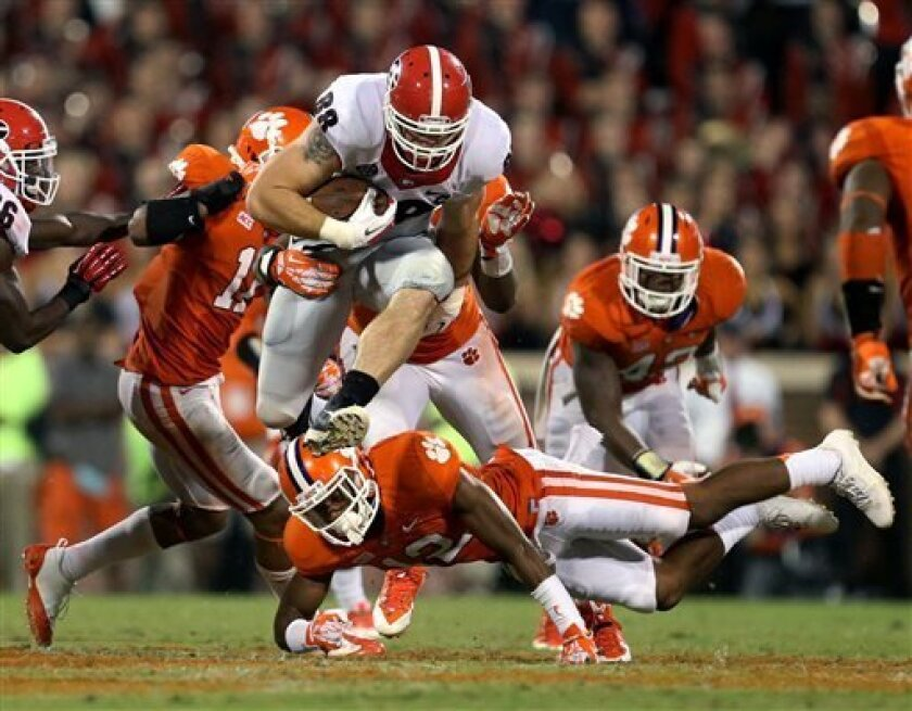 Georgia tight end Arthur Lynch (88) jumps over the tackle of Clemson safety Korrin Wiggins (12) after a catch in the second half of their NCAA college football game at Memorial Stadium, Saturday, Aug. 31, 2013, in Clemson, S.C. Clemson defeated Georgia 38-35. (AP Photo/Atlanta Journal-Constitution,