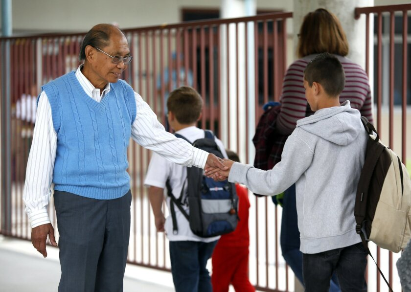 Jose Avila, better know as Grandpa Joe, greets students arriving at school earlier this year.