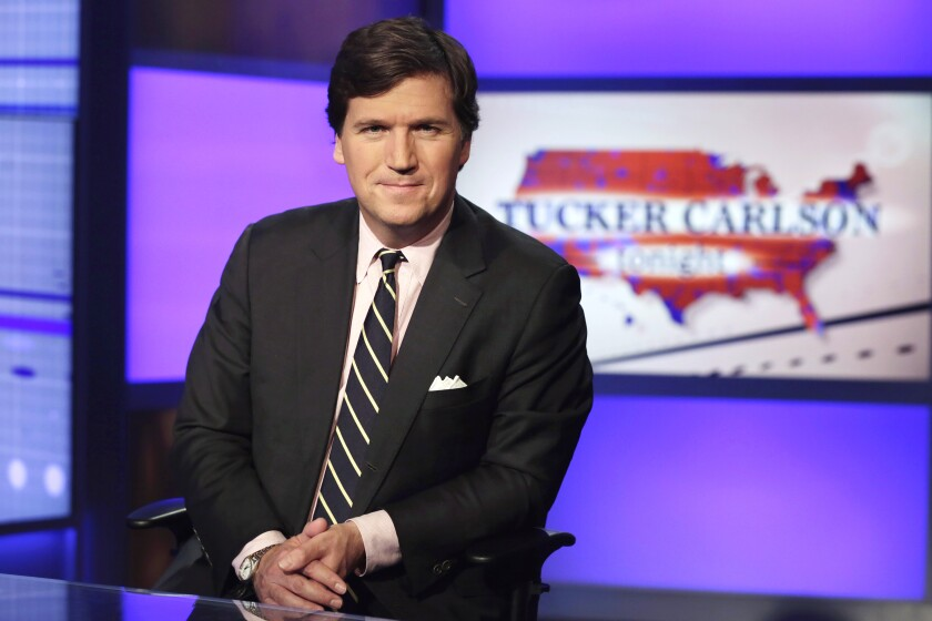 """FILE - In this March 2, 2017 file photo, Tucker Carlson, host of """"Tucker Carlson Tonight,"""" poses for photos in a Fox News Channel studio, in New York. The National Security Agency's internal watchdog said Tuesday it would investigate allegations that the agency """"improperly targeted the communications of a member of the U.S. news media"""" following Fox News host Tucker Carlson's claims that the NSA tried to shut down his show. (AP Photo/Richard Drew, File)"""