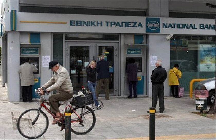 National Bank of Greece customers are seen outside a branch in Athens, Monday, April 8, 2013. Greek banks NBG and Eurobank are seeing their stock plunge 30 percent, the maximum allowed in a day, after news that their planned merger has been postponed. (AP Photo/Thanassis Stavrakis)