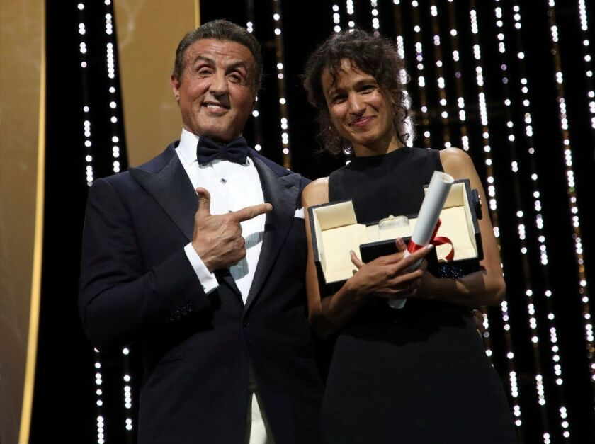 """Sylvester Stallone presented director Mati Diop, right, with the grand prix Palme d'Or award for the film """"Atlantique"""" (""""Atlantics"""") during the awards ceremony at the 72nd international film festival, Cannes."""
