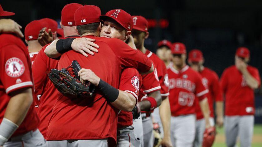 Angels' Kole Calhoun, center, hugs a teammate after the Angels' 9-4 win against the Texas Rangers in Arlington, Texas, on Tuesday.