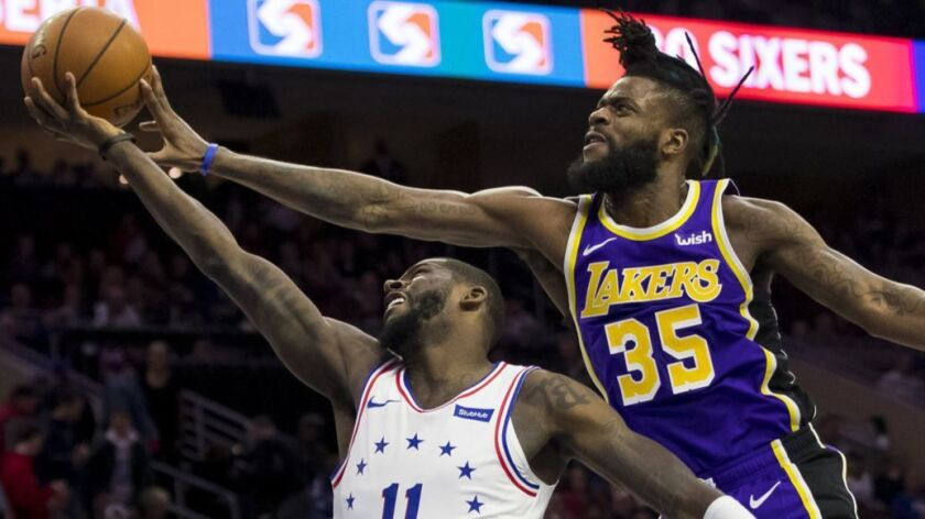 Los Angeles Lakers' Reggie Bullock, right, defends against a shot by Philadelphia 76ers' James Ennis