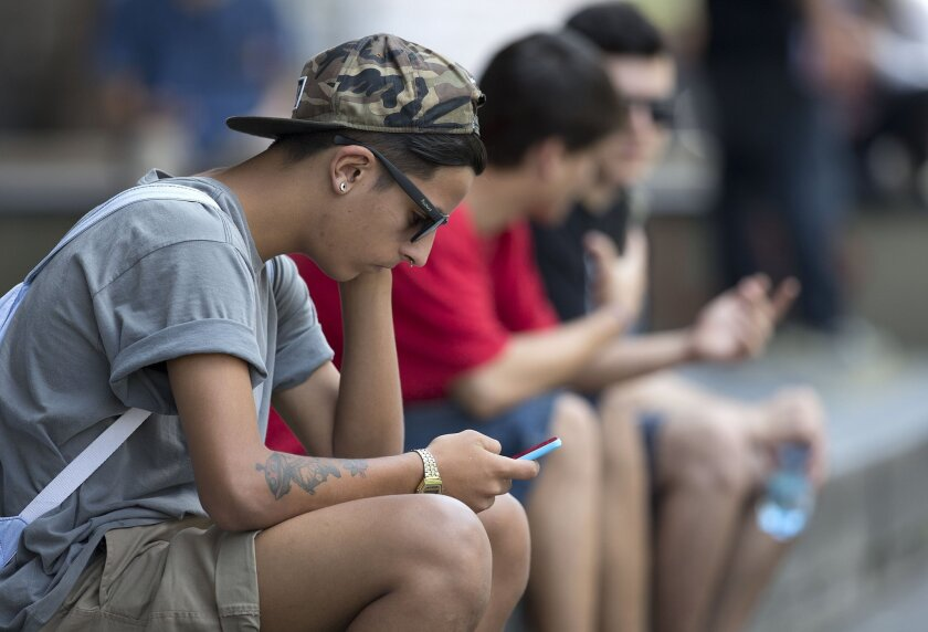 A youth checks his cell phone in Sao Paulo, Brazil, on Dec. 17.