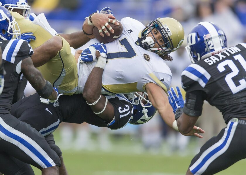 FILE - In this Sept. 26, 2015 file photo, Georgia Tech's Patrick Skov is upended by Duke's Breon Borders after picking up a first down during the second half of an NCAA college football game, in Durham, N.C. Georgia Tech's usually potent spread-option offense has come up flat in losses to Notre Dame and Duke. Now, as the Yellow Jackets prepare for a visit from North Carolina, coach Paul Johnson is looking for new options for his option attack. (AP Photo/Rob Brown)