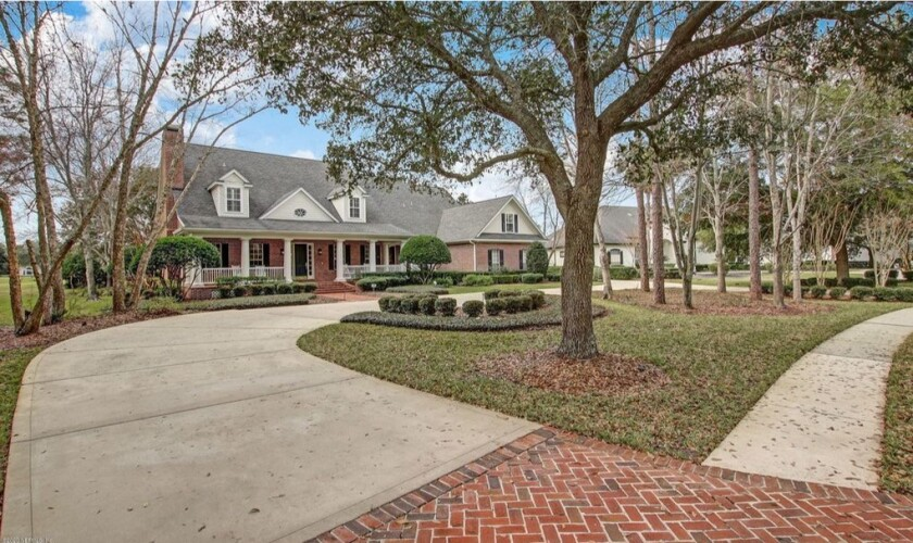 A brick home with a large driveway and lots of trees