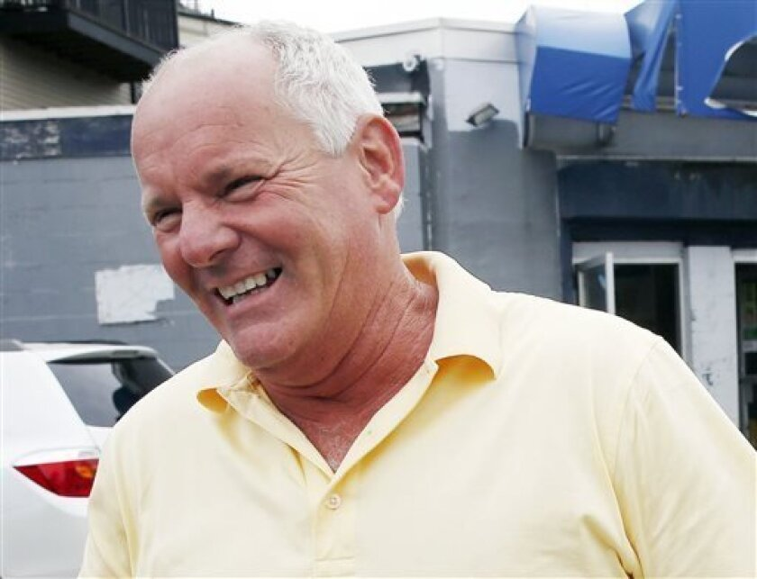 """FILE - In this June 6, 2013 photo, Stephen Rakes smiles outside the liquor store he once owned in the South Boston neighborhood of Boston. Rakes, who said he had been extorted by James """"Whitey"""" Bulger and hoped to testify at his trial, was given iced coffee laced with cyanide that killed him, authorities said Friday, Aug. 2, 2013, and that 69-year-old William Camuti, of Sudbury, is charged with attempted murder in his death. Rakes' body was found July 17 in the woods in suburban Boston the day a"""