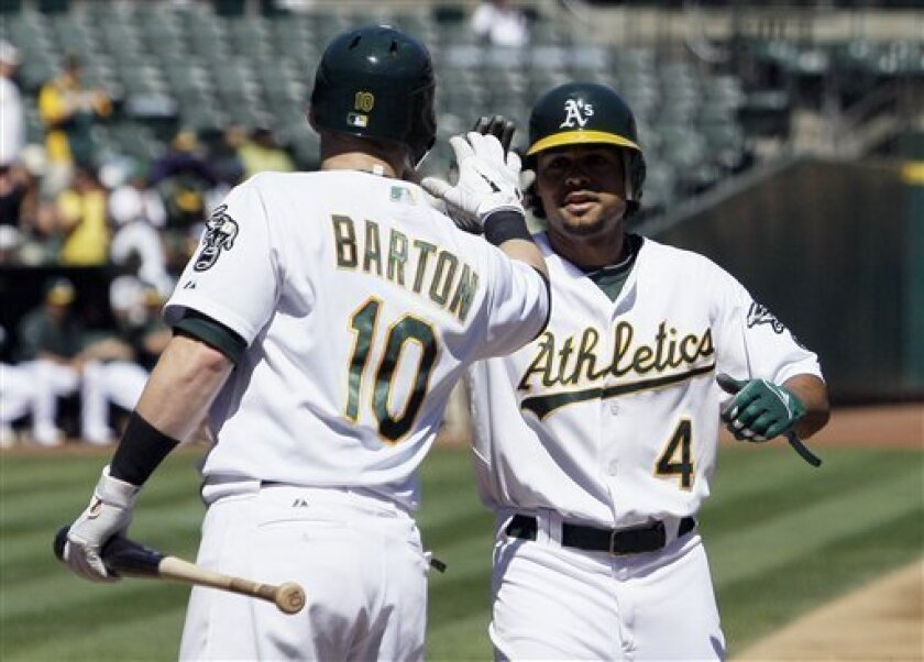Oakland Athletics' Coco Crisp, right, is congratulated by Daric Barton after hitting a solo home run against the Seattle Mariners in the first inning of a baseball game in Oakland, Calif., Monday, Sept. 6, 2010. (AP Photo/Jeff Chiu)