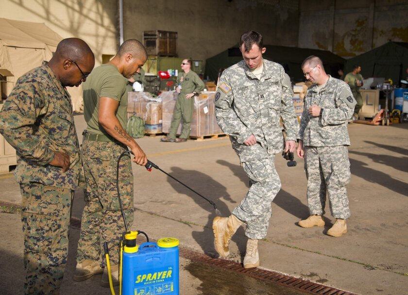 The Marines in Liberia in November 2014 sprayed their boots with bleach water to kill the Ebola virus and avoid contaminating other areas.