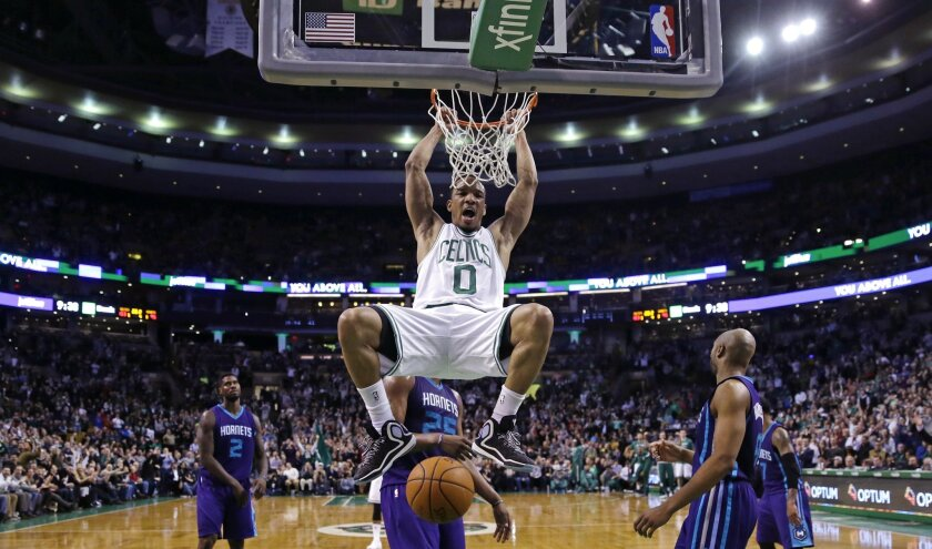 Boston Celtics guard Avery Bradley (0) hangs from the rim after slamming a dunk against the Charlotte Hornets during the second half of an NBA basketball game in Boston, Friday, Feb. 27, 2015. The Celtics defeated the Hornets 106-98. (AP Photo/Charles Krupa)