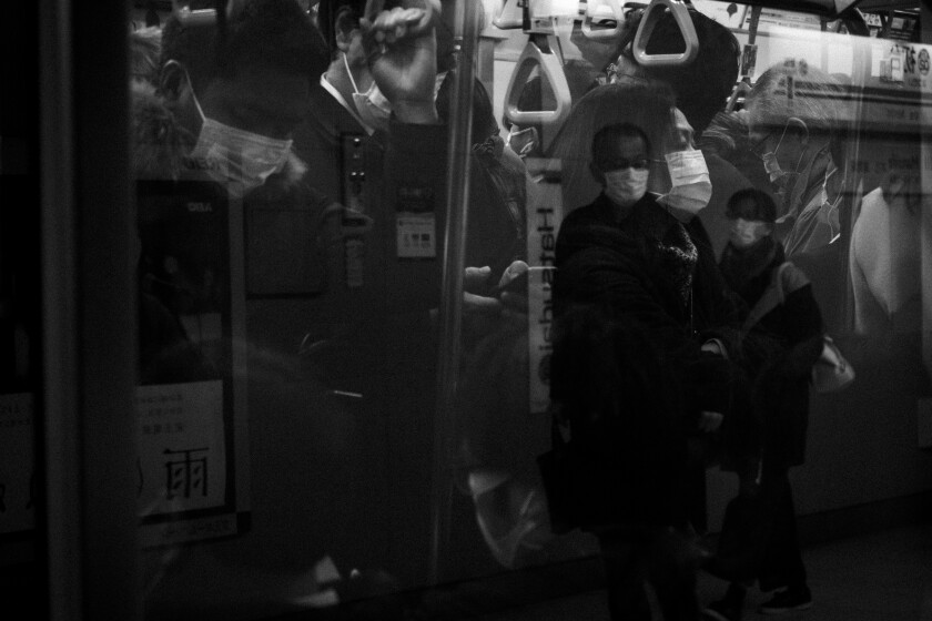 Commuters are reflected on the window of a packed train during morning rush hours in Tokyo, March 9, 2020. (AP Photo/Jae C. Hong)