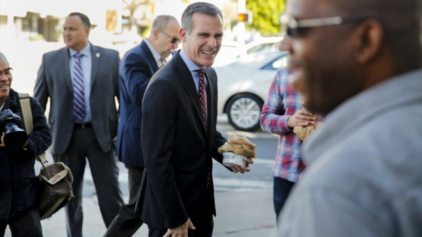 Los Angeles Mayor Eric Garcetti greets Craig Jones, who voted for him, outside the Noah's Bagels in Larchmont Village the morning after a decisive reelection this week.
