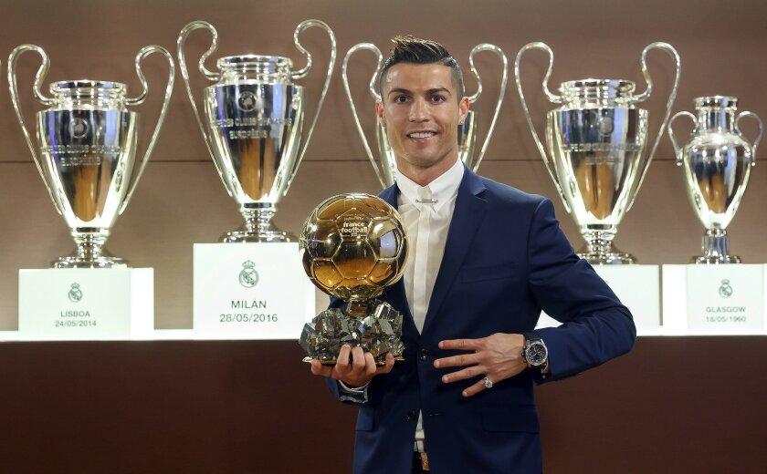 El jugador portugués del Real Madrid, Cristiano Ronaldo, posa con su cuarto Balón de Oro, ante otros trofeos del Real Madrid que están en la Sala de Juntas del estadio Santiago Bernabéu.