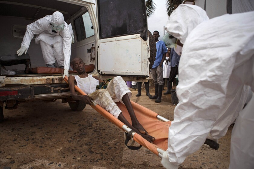 Healthcare workers load a man suspected of suffering from Ebola into an ambulance in Kenema, Sierra Leone, on Sept. 24