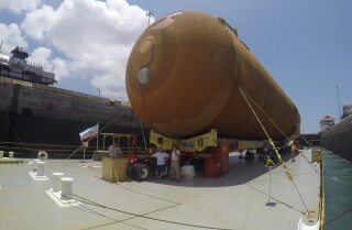 Space shuttle fuel tank, the last of its kind, travels through the Panama Canal