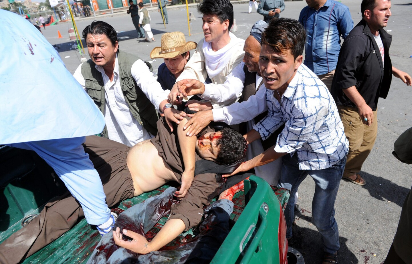 People transport victims' bodies after a suicide bomb attack in Kabul.