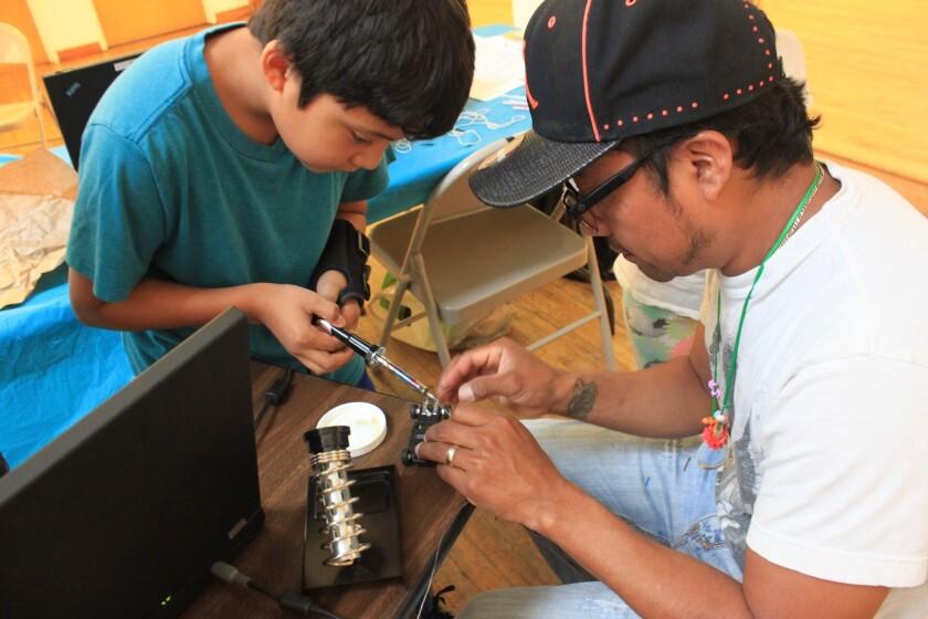 Un padre con su hijo realiza una práctica del taller de robótica desarrollado en el Centro de Recursos Centroamericanos (Carecen) en Los Ángeles.