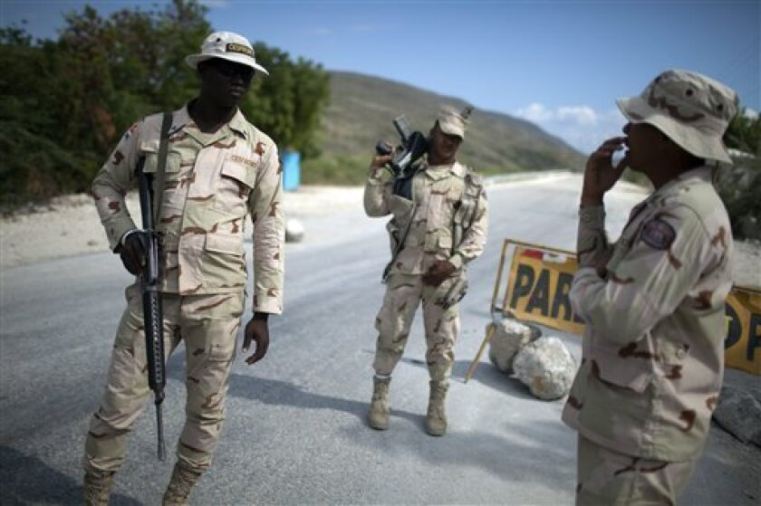 In this photo taken on Jan. 29, 2011, Dominican specialized military border officers stand guard at a checkpoint in Jimani, Dominican Republic. The largest campaign in years to deport Haitians living illegally in the Dominican Republic is causing widespread fear and prompting accusations that chole