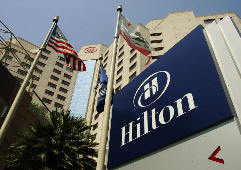 FILE - In this Tuesday, July 31, 2007, file photo, flags fly outside the Hilton Hotel in Long Beach, Calif., The hotelier, which went private in 2007, priced its initial public offering on Wednesday, Dec. 11, 2013 at $20 per share in the middle of its expected range, for a total take of $2.35 billion on the sale of 117.6 million shares. (AP Photo/Reed Saxon, File)