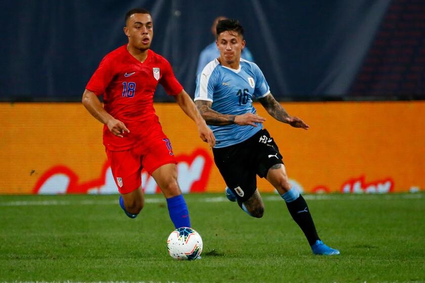 U.S. defender Sergiño Dest controls the ball ahead of Uruguay's Brian Rodriguez.