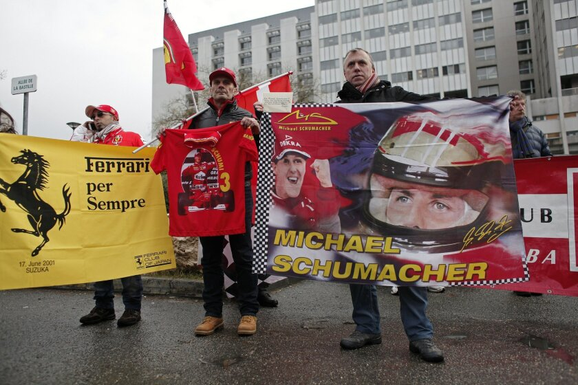 Fans of Michael Schumacher hold banners to honor the Formula One Champion on his 45th birthday, Friday Jan. 3, 2014, in front of the Grenoble hospital where former seven-time Formula One champion Michael Schumacher is being treated after sustaining a head injury during a ski accident. Schumacher ha