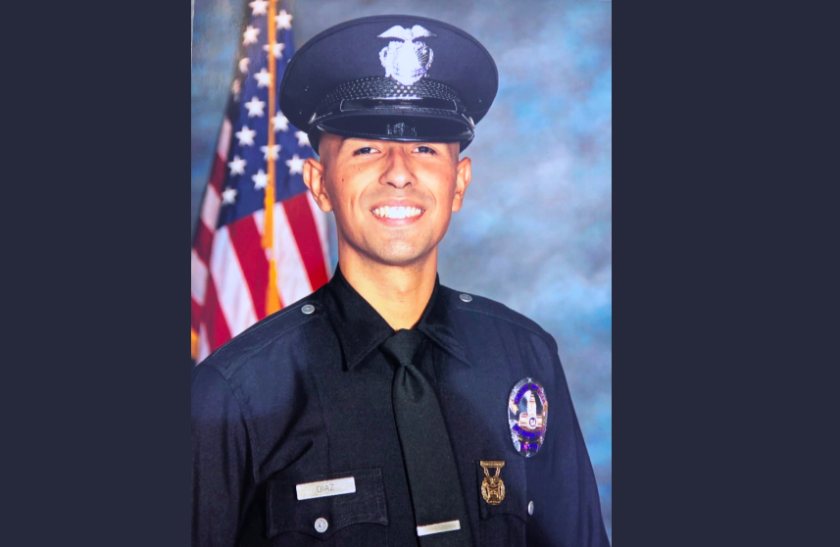 LAPD Officer Juan Jose Diaz in uniform with an American flag behind him.