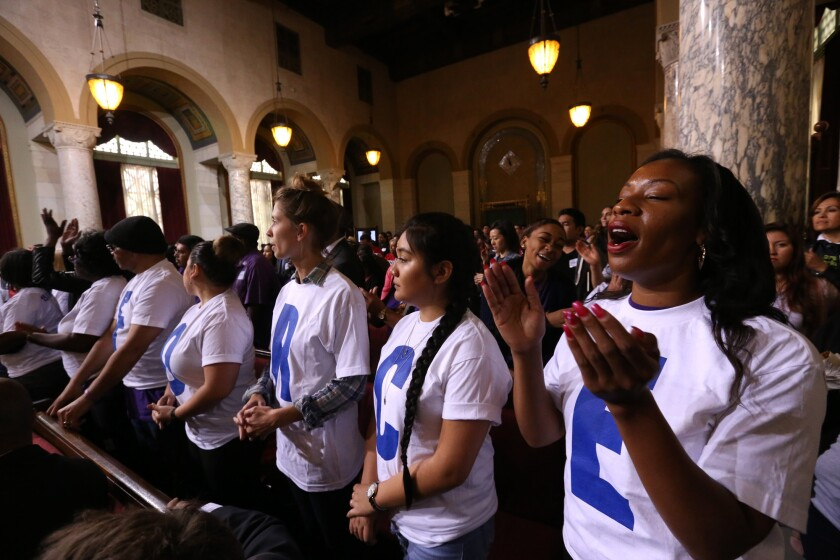 Members of SEIU United Service Workers West cheer before the Los Angeles City Council tentatively agreed to raise the city's minimum wage to $15 per hour by 2020 at City Hall on May 19.