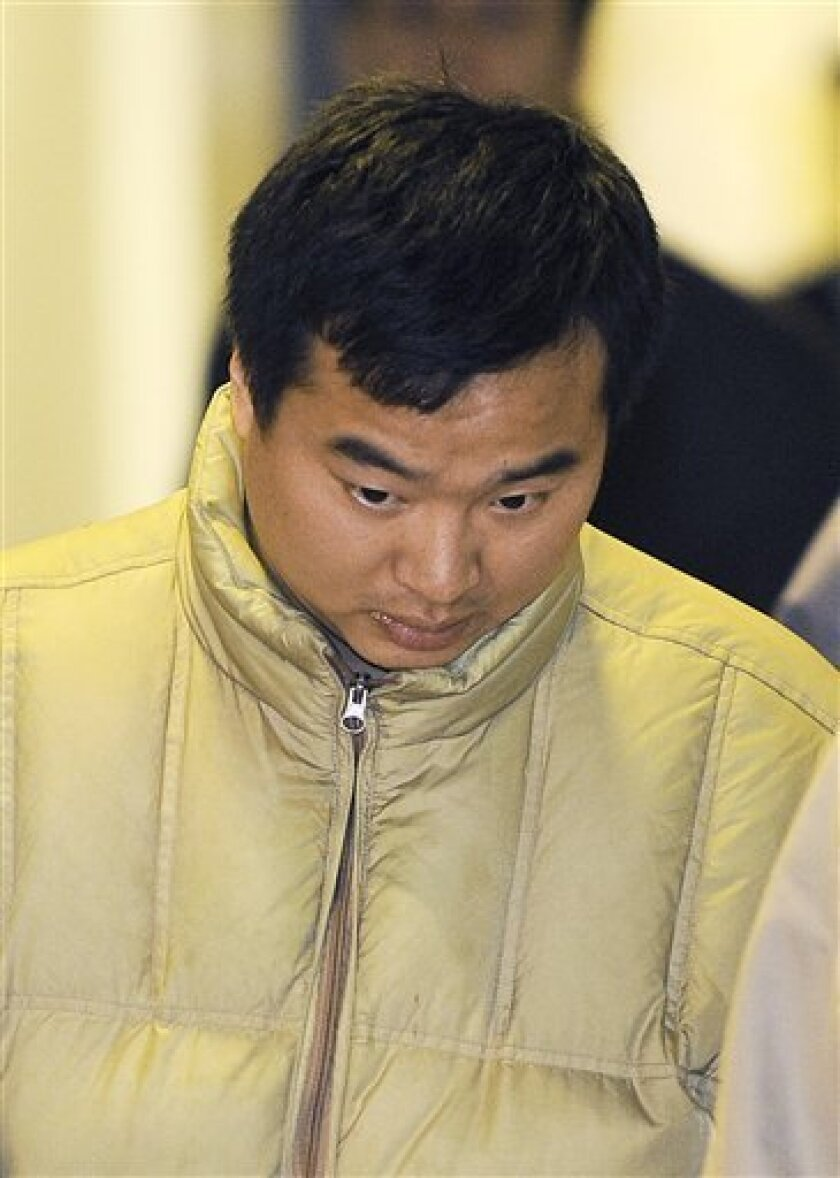 Haisong Jiang, 28, is shown being escorted out of the Port Authority Police building at Newark Airport in Newark, N.J., early Saturday Jan. 9, 2010. Jiang, believed to have breached security to bid his girlfriend goodbye, triggering the shutdown of a busy Newark Airport terminal that led to snarled flights worldwide, was arrested in New Jersey and faces a trespassing charge and a fine of up to $500, punishment a senator says should be much harsher. (AP Photo/Joe Epstein)