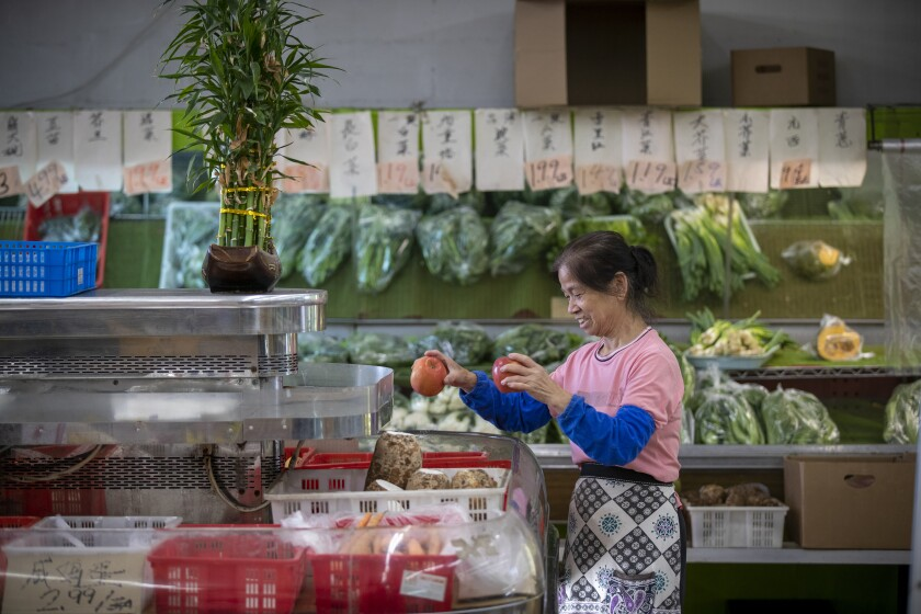 A. Choi arranges fruit on display at G and G Market in Chinatown