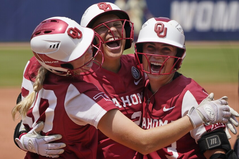 Oklahoma's Jayda Coleman, center, celebrates at home plate with teammates Jana Johns, left, and Grace Lyons, right, following her home run against Florida State in the second inning of the final game of the NCAA Women's College World Series softball championship series Thursday, June 10, 2021, in Oklahoma City. (AP Photo/Sue Ogrocki)