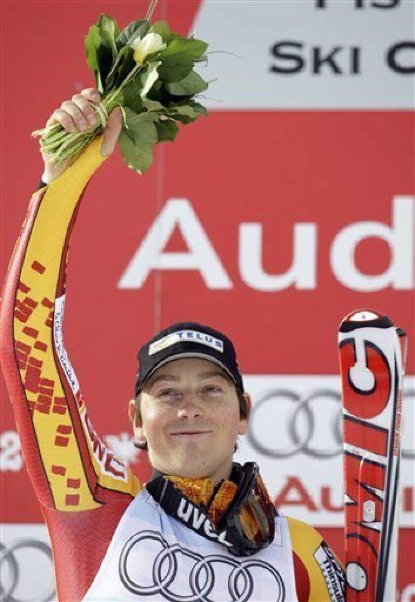 Canada's John Kucera celebrates on the podium after winning the Men's Downhill race, at the World Alpine Ski Championships in Val d'Isere, France, Saturday, Feb. 7, 2009. (AP Photo/Sergey Ponomarev)