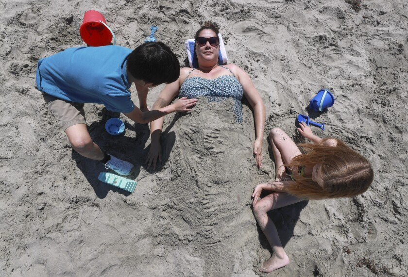 Sophia Balangue is covered with sand by son Liam, 8, and friend Riley Sunblad, 7, during a pre-restrictions March visit to Oceanside City Beach.