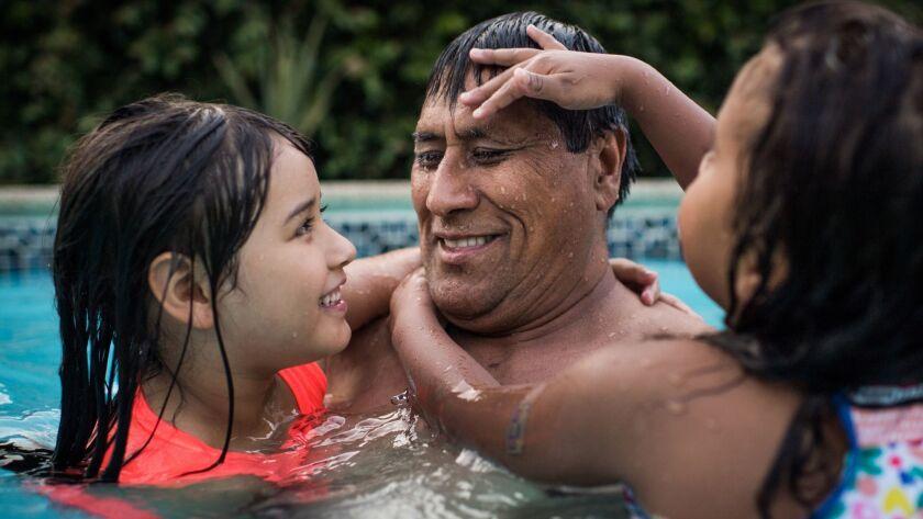 ARLETA, CA - July 4, 2018 A week after his release, Jose Garcia plays with his granddaughters at hi