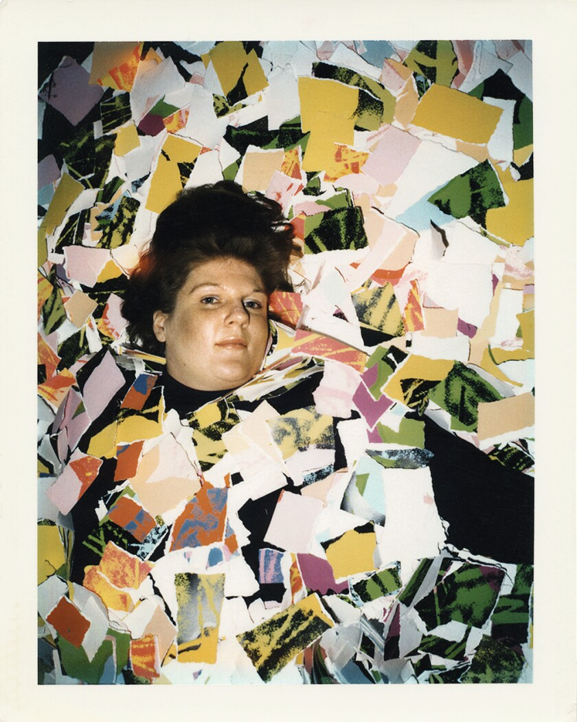 A self-portrait by Brigid Berlin lying amid scraps of colored paper