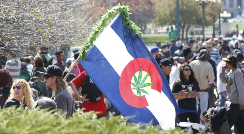 A man carries a modified version of the state flag of Colorado during activities on the unofficial marijuana holiday on April 20 in Denver.