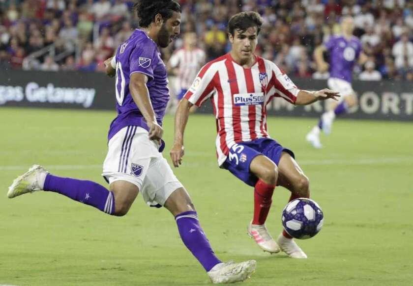El delantero mexicano de Los Angeles FC Carlos Vela (i) intenta un tiro ante el defensa del Atlético de Madrid, Manu Sánchez, en el Juego de las Estrellas de la MLS en Orlando, Florida.