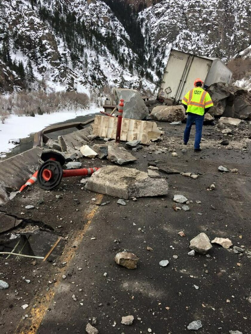 In this photo provided by the Colorado Department of Transportation a highway worker examines debris from a rock slide on Interstate 70 in Glenwood Canyon in western Colorado on Tuesday, Feb. 16, 2016. The rocks damaged the tractor-trailer rig visible in the background, but state officials said no