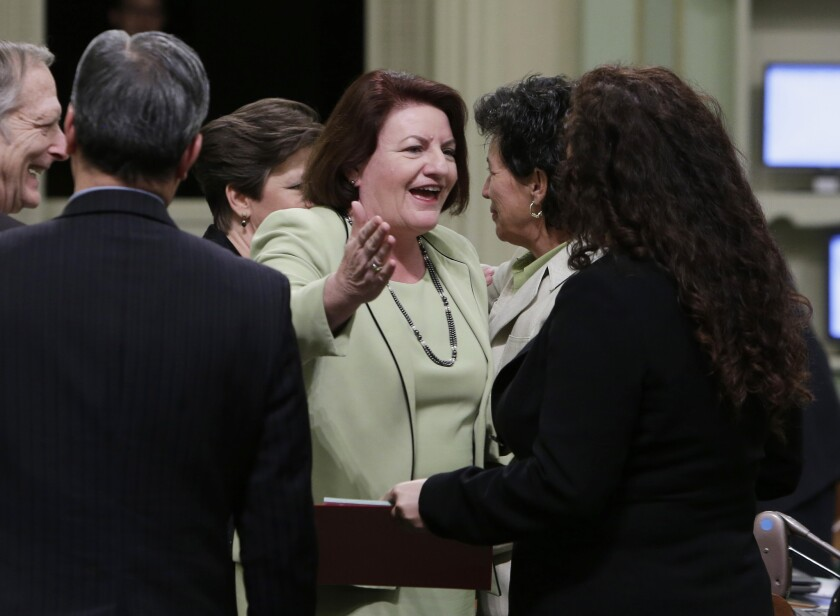 Assemblywoman Toni Atkins (D-San Diego), center, is congratulated by Assemblywoman Lorena Gonzalez (D-San Diego), right, after she was elected Assembly speaker at the Capitol in Sacramento. By a unanimous voice vote, Atkins was elected to replace Speaker John Pérez (D-Los Angeles). Perez says a transition date has not been set but that it will be before summer.