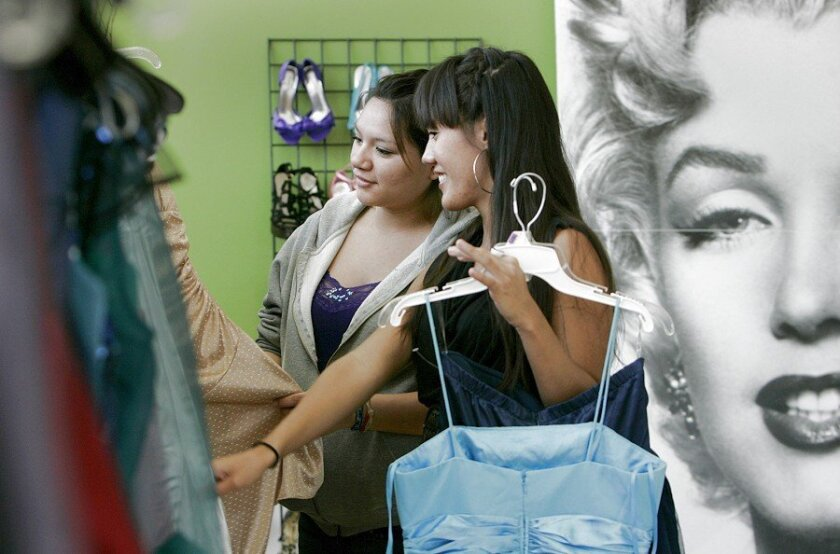 Stephanie Gutierrez, 17, left, chose a few prom dresses to try on Sunday, with help from volunteer Spring Cretton.