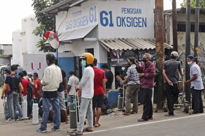 People wait for their turn to refill their oxygen tanks at a recharging station in Jakarta, Indonesia, Friday, July 9, 2021. Just two months ago, Indonesia was coming to a gasping India's aid with thousands tanks of oxygen. Now, the Southeast Asia country is running out of oxygen as it endures a devastating wave of coronavirus cases and the government is seeking emergency supplies from other countries, including Singapore and China. (AP Photo/Tatan Syuflana)