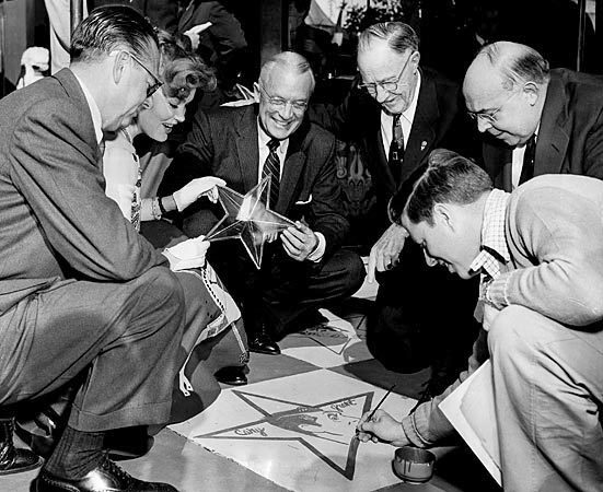 Taking an early stab at envisioning what would become the Hollywood Walk of Fame, artist Jack Lane, right, puts the finishing touches on a painted star framing a celebrity's caricature on the sidewalk in front of Grauman's Chinese Theatre on Hollywood Boulevard in February 1956. Others, from left, are Edwin Zabel, general manager of Fox West Coast Theaters; actress Kipp Hamilton; A.E. England, president of the Hollywood Chamber of Commerce; Los Angeles City Councilman Earle Baker; and E.M. Stuart, the driving force behind creation of the Walk of Fame and later a Hollywood Chamber of Commerce president himself.